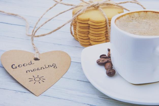 泡、ジンジャーブレッドクッキー、おはようメモとブラックコーヒーのカップ