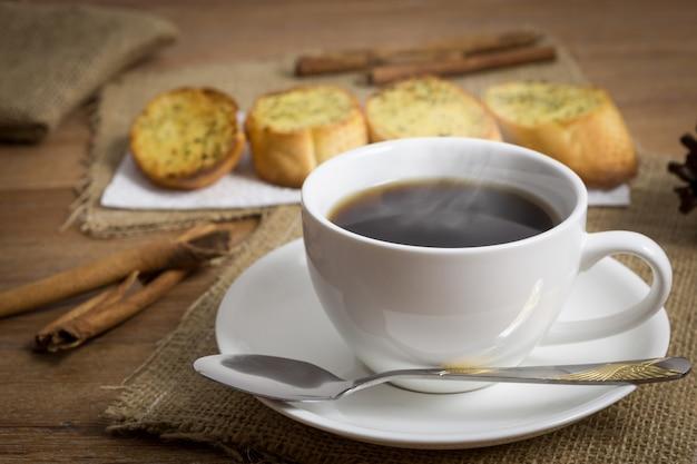 나무 테이블에 마늘 빵을 곁들인 블랙 커피 한 잔, 아침 시간을 위한 커피, 마늘 빵