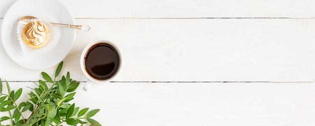 白いテーブルの上のミニケーキとブラックコーヒーのカップ。