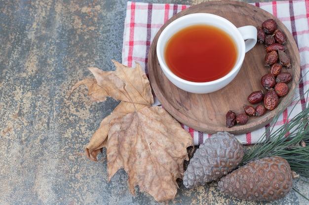 紅茶と松ぼっくりの木製プレートに乾燥したローズヒップのカップ。高品質の写真