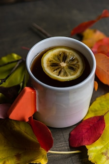 コピースペースと木製の背景に紅茶とレモンのカップ