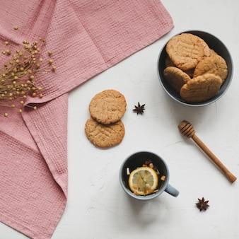 Чашка черного чая с лимонным домашним печеньем и скатертью на белой деревенской поверхности