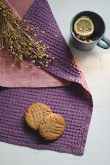 白い素朴な表面に紅茶レモン自家製クッキーとテーブルクロスのカップ