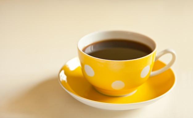 노란색 접시에 홍차 한잔입니다. 점이 있는 노란색 컵. 레트로 스타일. 빈티지 옐로우 머그