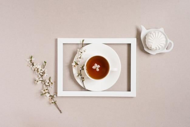 Чашка черного чая с цветками яблони в белой рамке и вид сверху белой чашки на бежевом фоне