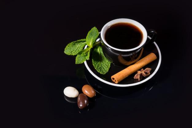 단색 검정 배경 위에 향료 옆에 바닐라와 초콜릿 캔디가 들어간 홍차 한잔