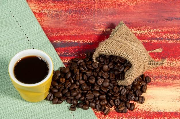 볶은 콩이 녹슨 테이블에 떨어지는 가방 옆에 있는 브라질 커피 한 잔