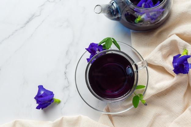 テーブルの上に蜂蜜とバタフライエンドウ豆フラワーティーのカップ