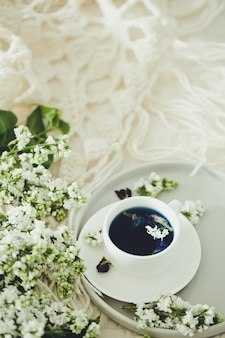 健康的な飲用、デトックス飲料、白いライラック用のバタフライピーティー(エンドウ豆の花、ブルーピース)のカップ。