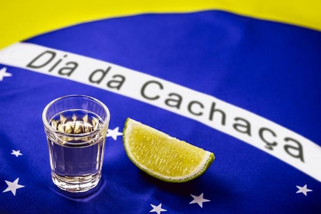 カシャーサまたはブラジルのピンガのカップ、背景にブラジルの国旗、ポルトガル語のテキスト:カシャーサの日