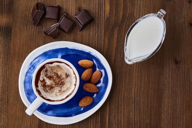 Чашка капучино, миндаль, шоколад и молоко в стеклянном кувшине для молока на темном деревянном столе