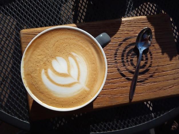 晴れた日のカフェでのカプチーノのカップは、グリッドメタルテーブルの木製トレンチャーで提供されます朝をお楽しみください