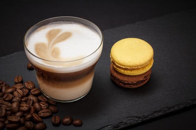 黒い石のボードにカプチーノ、コーヒー豆、マカロンのカップ。上面図。