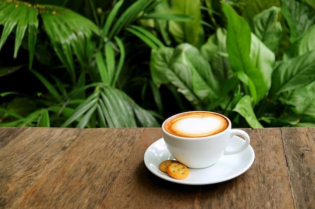 背景に緑豊かな庭園と木製のテーブルの上のカプチーノコーヒーのカップ