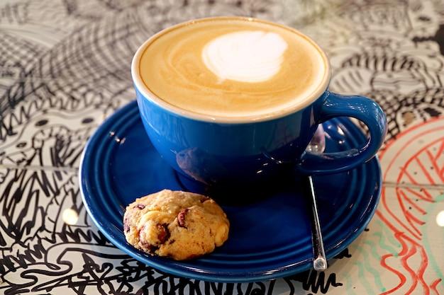チョコレートチップクッキーとカプチーノコーヒーのカップ