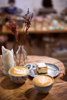 Чашка капучино с тортом на деревенском деревянном столе. керамическая чашка ручной работы. керамика чашка для капучино