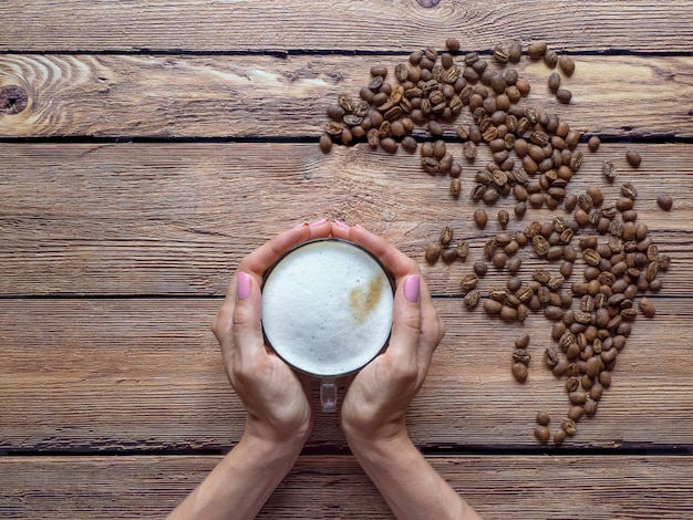 손에 카푸치노 한잔입니다. 나무 배경에 커피 콩 프리미엄 사진