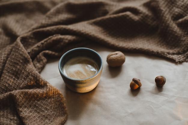 Чашка капучино на фоне текстуры коричневой бумаги с уютными теплыми клетчатыми грецкими орехами и желудями