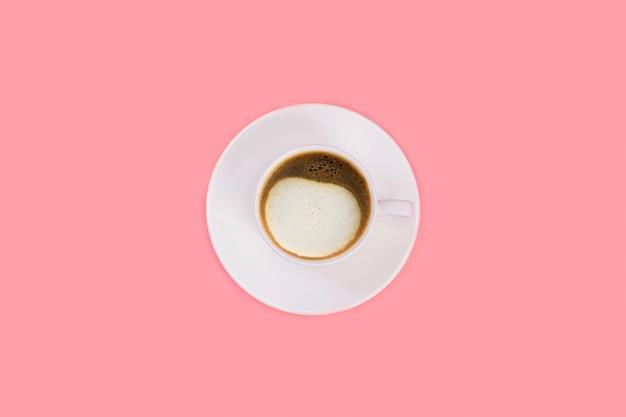 Чашка капучино на белом блюдце на розовом фоне. вид сверху, плоская планировка, копия пространства