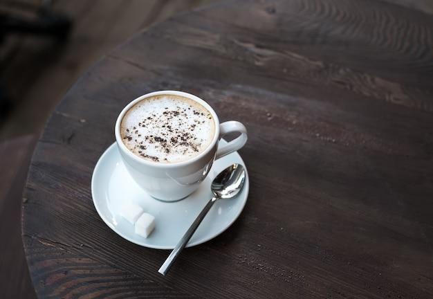 古い暗い木製のテーブルにカプチーノのカップ