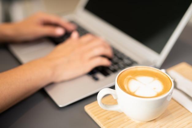 カフェでネットワーク中にラップトップのキーパッドに触れる女子学生の手の横にある木製トレイにカプチーノのカップ