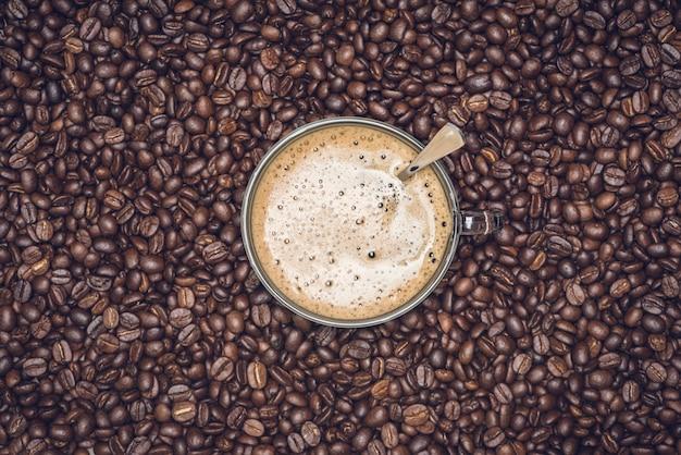 ローストフルフレームコーヒー豆の背景を持つコーヒー豆のプレートに配置されたカプチーノのカップ
