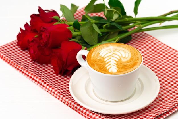 アートと木製のテーブルの上のバラの花束とカプチーノのカップをクローズアップ
