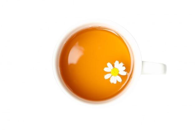 白で隔離されるカモミールティーのカップ