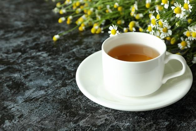 Чашка ромашкового чая на черном дымчатом столе