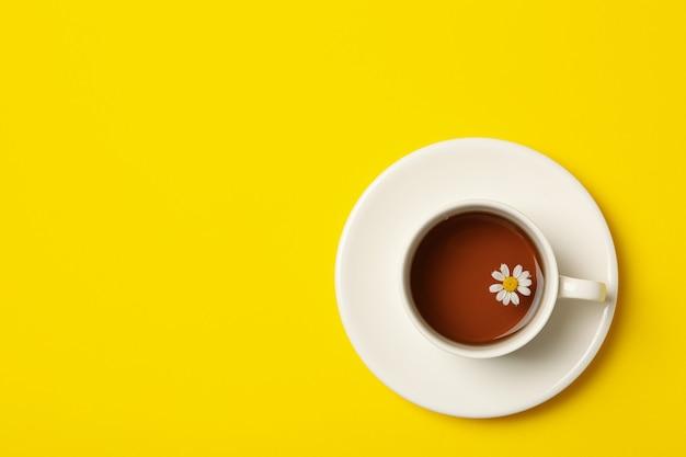 黄色の背景にカモミールティーのカップ