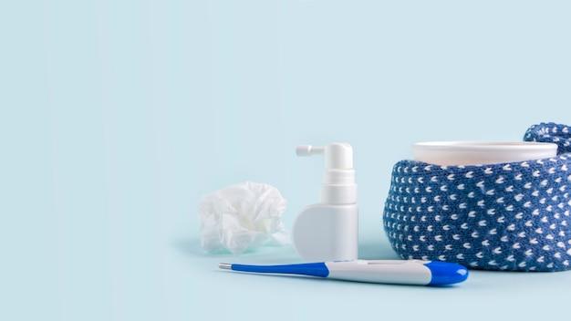 카모마일 차, 온도계, 구겨진 냅킨, 그리고 파란색 배경에 콧물과 목을 위한 스프레이. 계절성 질병 및 감기, 독감, 더위 치료. 바이러스 예방, 배너