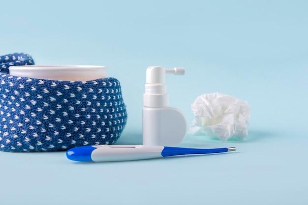 카모마일 차, 온도계, 구겨진 냅킨, 그리고 파란색 배경에 콧물과 목을 위한 스프레이. 계절성 질병 및 감기, 독감, 더위 치료. 바이러스 예방.