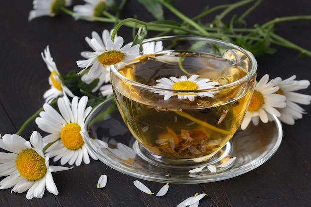 木製の板にカモミールの花とカモミールティーのカップ