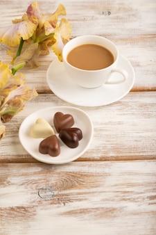 흰색 나무 표면에 초콜릿 사탕, 라일락, 보라색 아이리스 꽃이 든 cioffee 한 잔.