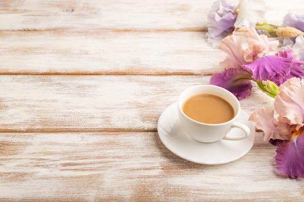흰색 나무 바탕에 라일락과 보라색 아이리스 꽃을 넣은 cioffee 한 잔. 측면보기, 복사 공간,
