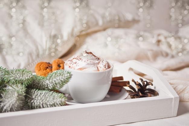 冬の早朝、ベッドの上の白いトレイにココアのカップ