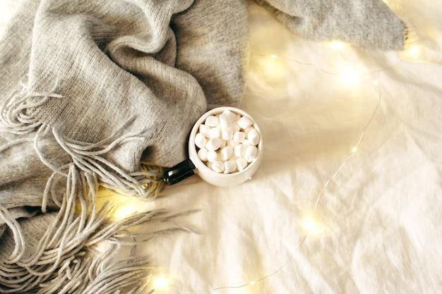 Чашка какао с зефиром, шарф, сверкающие огни на белой простыне. рождество, зима, новогодняя композиция. плоская планировка, вид сверху, копия пространства.