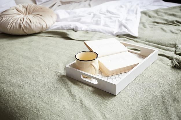 一杯のコーヒーとトレイの本。現代的なベッドルームのインテリアのキングサイズのベッドにベージュと白の寝具。寝室のアイデア