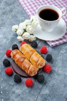 Чашка кофе вместе со сладкими вкусными браслетами и ягодами на сером столе, сладкая выпечка, сахарный торт