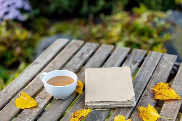 一杯のコーヒーと庭の木製テーブルの本