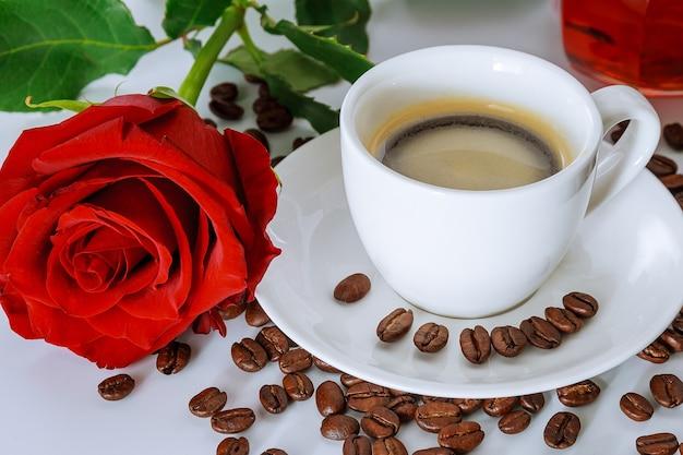 一杯のコーヒーと赤いバラの花束。テーブルの上に散らばったコーヒー豆。おはようございます。