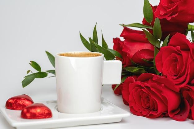 一杯のコーヒーと白いテーブルの上の赤いバラの花束