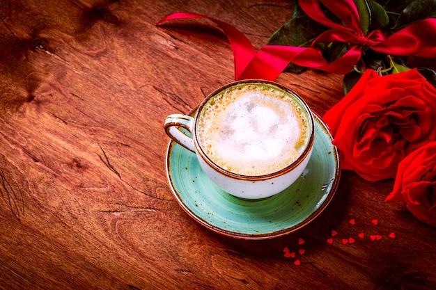 Чашка кофе и букет красных роз на деревянном фоне, свободное место для текста