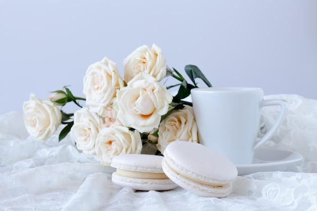 一杯のコーヒーと白いバラの花束