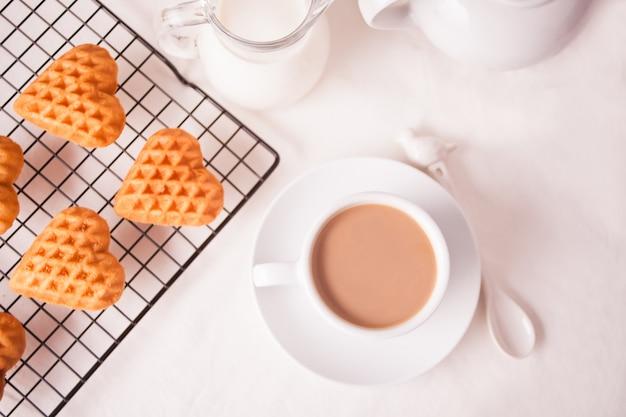 Чашка кофе и печенье в форме сердца на противень