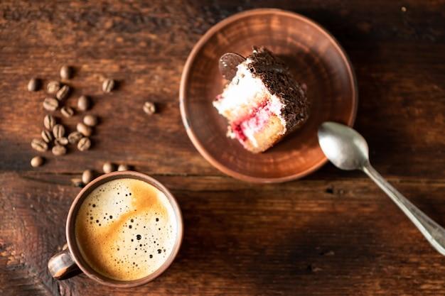어두운 나무 배경에 커피 한 잔과 케이크 한 조각.