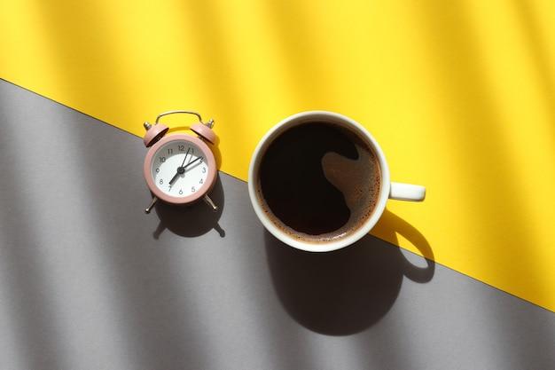 深い影とトレンディな黄色と灰色の背景にコーヒーと目覚まし時計のカップ朝のコンセプトを目覚めさせる