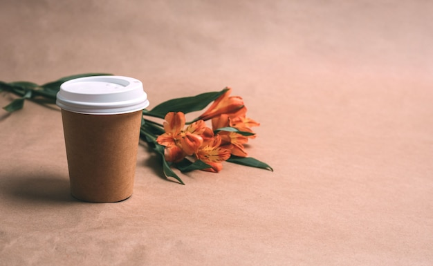 クラフトの背景にコーヒーとアルストロメリアのカップ