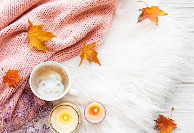 毛皮の背景に一杯のコーヒーと紅葉
