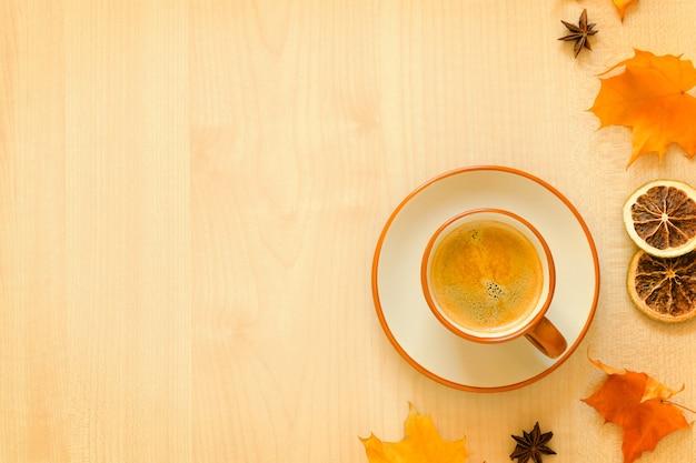 一杯のコーヒーと木製の背景に紅葉。